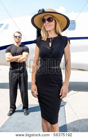 Happy woman in elegant dress with bodyguard and private jet in background