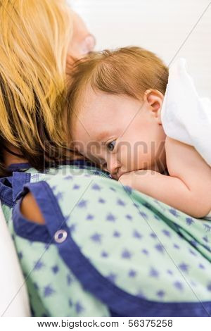 Closeup of cute newborn babygirl lying on mother in hospital