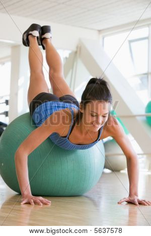 Woman Doing Push Ups On Swiss Ball At Gym