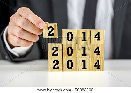 Businessman With 2014 New Year Building Blocks