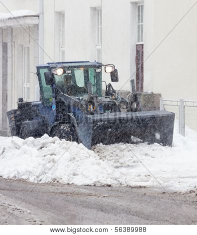 Snowplow cleaning a city street in snowfall