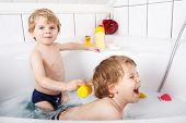 stock photo of bubble-bath  - Two adorable little twin boys having fun with water by taking bath in bathtub - JPG