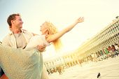 Romantic couple in love having fun embracing and laughing in Venice, Italy on Piazza, San Marco. Hap