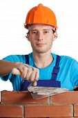 stock photo of putty  - A bricklayer in orange helmet holding a putty knife - JPG
