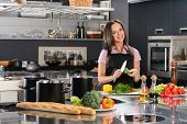 stock photo of apron  - Happy young woman in apron on modern kitchen cutting vegetables - JPG