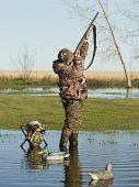 stock photo of duck  - A young hunter taking aim at a duck - JPG