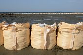 stock photo of sandbag  - big sandbags for protection against a blue sky - JPG
