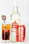 HAVANA,CUBA - DECEMBER 25, 2013:Havana Club rum bottle and coke can next to a Cuba Libre coktail.Est