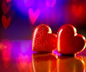 Valentine Heart. Couple of Valentines Red Hearts over Abstract Purple Bokeh Background. Love Concept