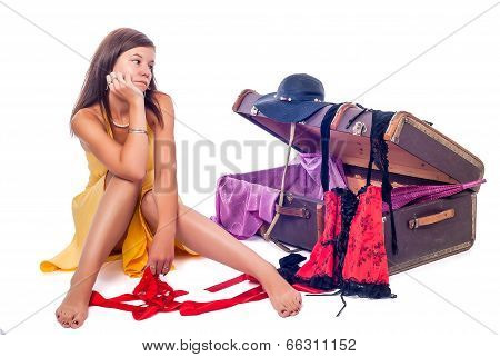 Pretty girl reflected before an open suitcase