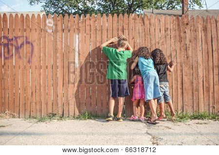 Kids peeking through a fence