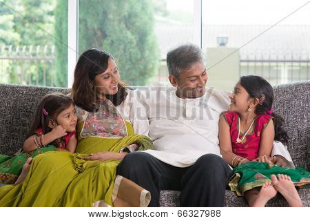 Happy Indian family at home. Asian parents chit chatting with their kids, sitting on sofa. Parents and children indoor lifestyle.