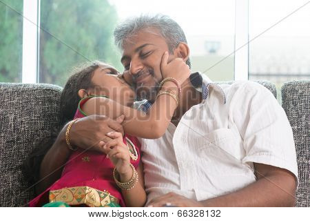Happy Indian family at home. Asian sweet daughter kissing her father face indoor, sitting on sofa.