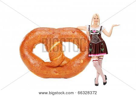 Full length portrait of a Bavarian girl leaning on an enormous pretzel isolated on white background