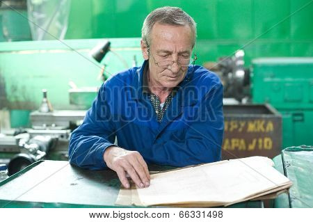 Elderly worker looks in drawing