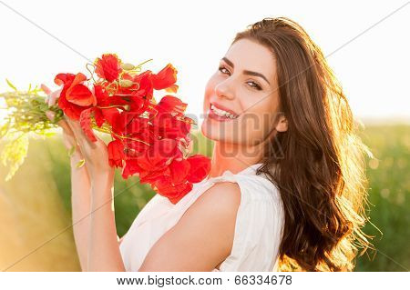 Beautiful lady over Sky and Sunset in the field holding a poppies bouquet, smiling