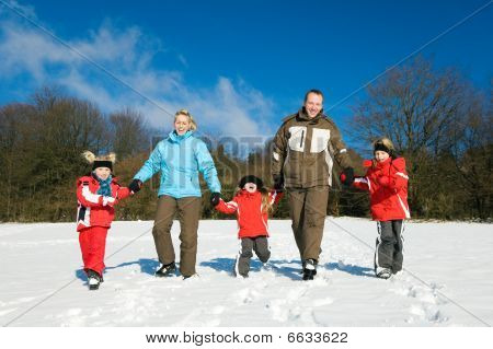 Active family having a winter walk in the snow