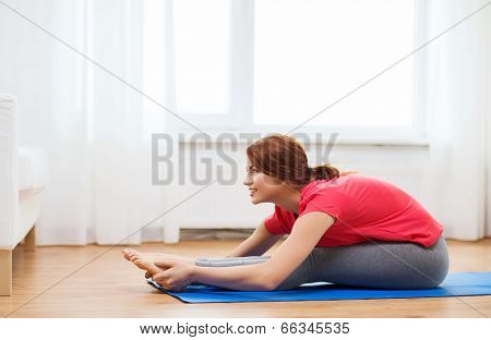 fitness, home and diet concept - smiling teenage girl streching on floor at home