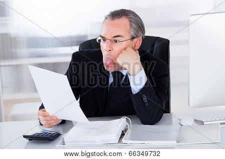 Mature Businessman Sticking Tongue Out