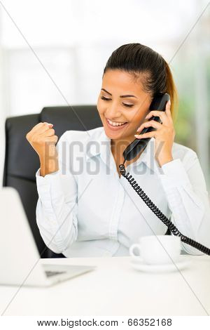 happy businesswoman receiving exciting news over the phone