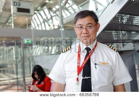 BANGKOK - OCT 27: Airasia pilot posing in Bangkok Airport on October 27, 2011 in Bangkok, Thailand. AirAsia Berhad is a Malaysian low-cost airline headquartered in Kuala Lumpur, Malaysia