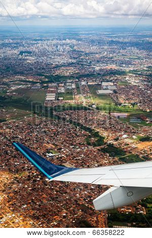 aerial view over big city with airplane wing