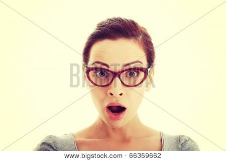 Young casual woman in eyeglasses expresses shock