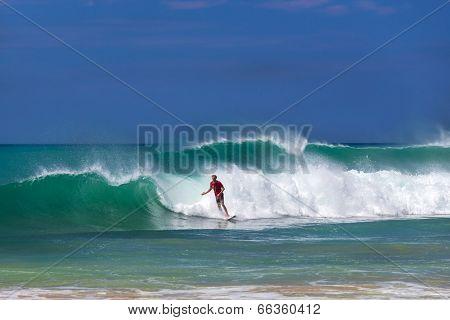 HIKKADUWA, SRI LANKA - FEBRUARY 24, 2014: Surfer riding a wave on Hikkaduwa beach, well known tourist international destination for board surfing.