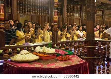 KANDY, SRI LANKA - FEBRUARY 26, 2014: Group of tourists inside the Temple of the Tooth. The Sacred Tooth Relic of the Buddha attracts thousands of pilgrims and tourists to the sacred city of Kandy.