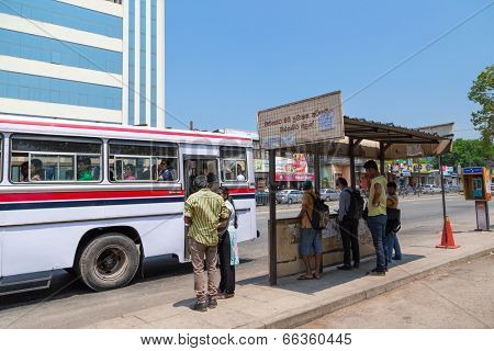 COLOMBO, SRI LANKA - FEBRUARY 22, 2014: Local people at bus stop waiting for bus. Buses are the Sri Lankan principal mode of public transport.