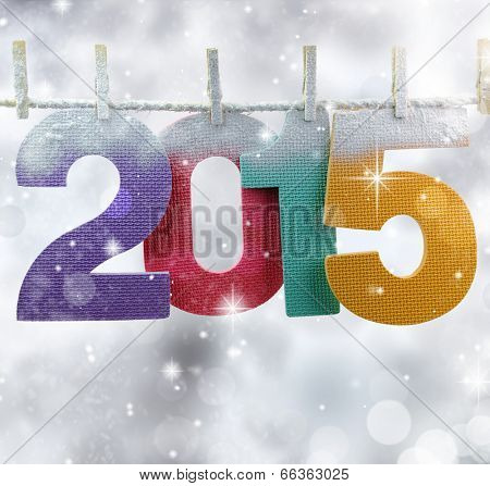 Number 2015 hanging on a clothesline in a glittery lights background