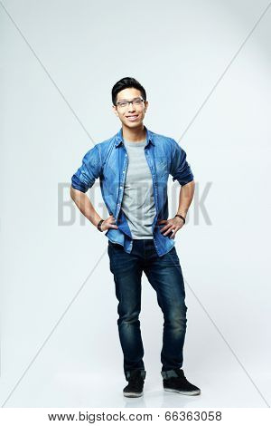 Full-length portrait of a young happy asian man on gray background
