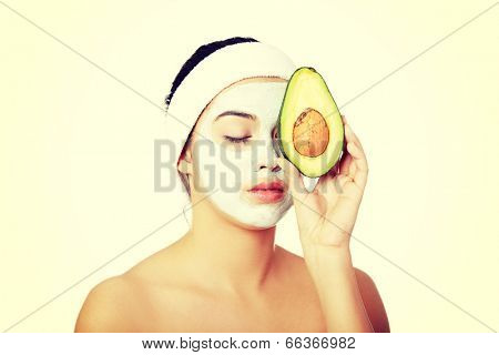 Young woman holding avocado heaving face clay mask on the face in a spa