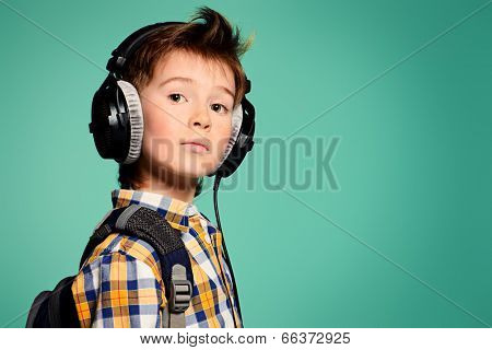 Cute 7 year old boy listening to music on headphones. Copy space.