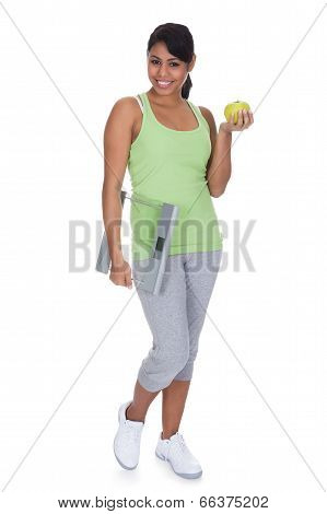 Portrait Of Woman Holding A Weighing Scale And An Apple