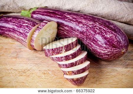 two fresh eggplants on wooden board