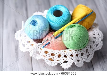 Colorful clews, napkin and crochet hook in wicker basket, on wooden background