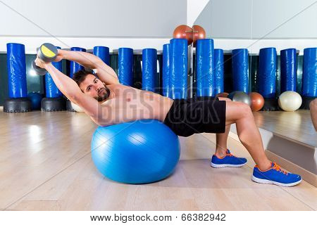 Dumbbell bench press on fit ball man workout at fitness gym