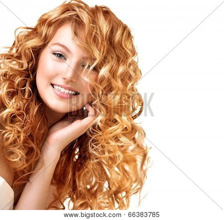 Beauty teenage model girl portrait isolated on white background. Red curly hair. Healthy wavy hair. Hairstyle. Beautiful smiling young woman portrait. Beautiful face, natural make up. Long permed hair