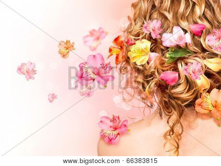 Hairstyle with colorful flowers. Beautiful healthy curly hair decorated with flowers.Over blurred pink background. Hair care concept. Backside view. Long permed hair style