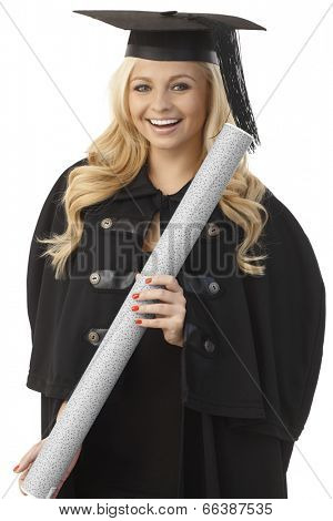 Happy female graduate in academic dress holding diploma, smiling.