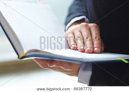 Female hands holding notebook.