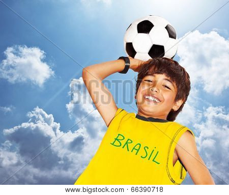 Boy playing football outdoor, happy child, teen goalkeeper enjoying sport game, holding ball, portrait of a preteen smiling and having fun, kids activities, little footballer over blue sky background