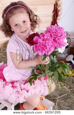 Beautiful small girl in petty skirt holding flowers on country style background