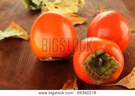 Ripe persimmons with yellow leaves on wooden background