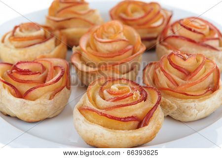 Tasty puff pastry with apple shaped roses on plate close-up