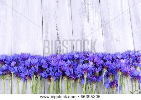 Beautiful cornflowers on wooden background