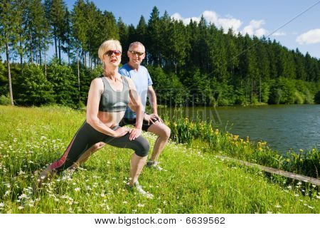 Mature or senior couple in jogging gear doing sport and physical exercise outdoors, stretching and g