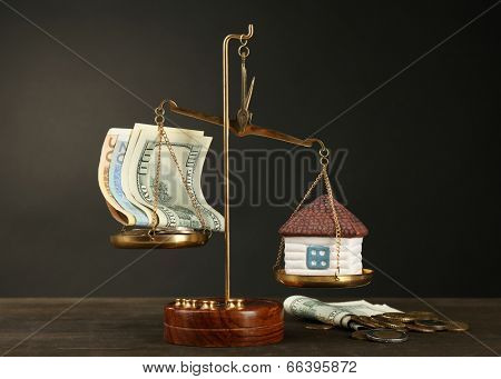Scale with money and model of house on dark background