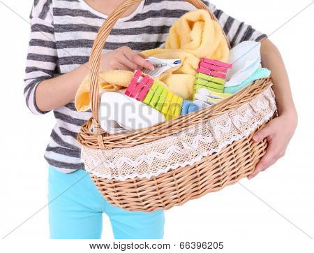 Woman holding laundry basket with clean clothes, towels and pins, isolated on white